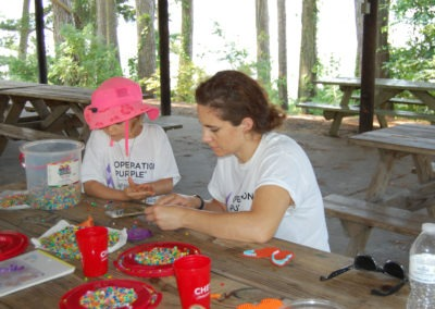 Woman and girl doing arts and crafts at a picnic bench at Buddy Camp