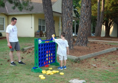 Man and boy playing a giant Connect Four game outside at Buddy Camp