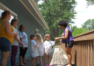 Girl petting a turtle with other participants outside on a deck at Buddy Camp